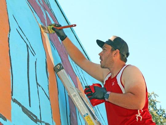 Local artist Ben Schuh paints a mural on Saturday,