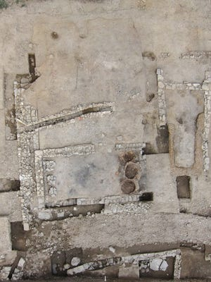 Overhead view of a possible ancient tavern, with three reddish circles marking the bread ovens and pebbles marking built-in benches in the dining room at the right.
