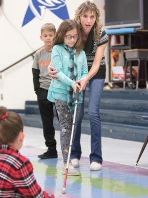 Stephanie Davis has 7-year-old Isabella Musacchia keep her eyes closed and shows her how navigate using a white cane during a presentation for the second graders at S.S. Dixon Primary School in Pace on Thursday.