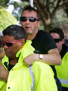 Phil Rudd, center, drummer for the rock band AC/DC, jumps onto the back of his security guard after his short court hearing in the High Court at Tauranga, New Zealand, Wednesday. The 60-year-old is charged with threatening to kill, which comes with a maximum prison sentence of seven years, as well as possessing methamphetamine and marijuana.