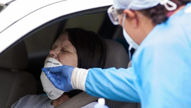 Regina Nelson, left, is tested for the coronavirus by Gina Johnson, a nurse tech, at the Bono Family Medical Clinic drive-thru testing site on Friday, April 24, 2020, in Bono, Ark.