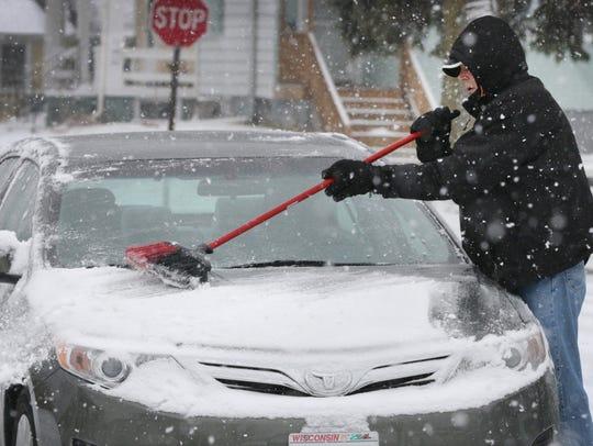 Jerry Hirt of Sheboygan brushes snow off his car.