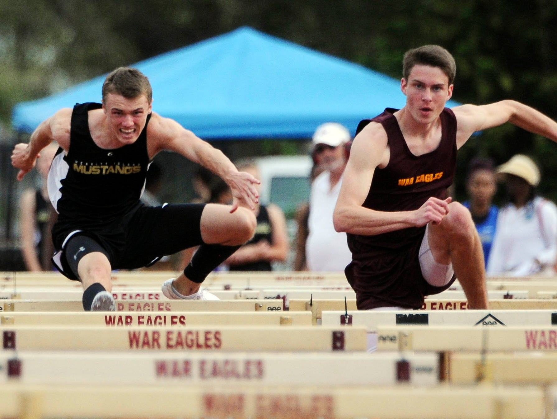 Jimmy Batch of Merritt Island battles Tristan Schultheis of Astronaut for the lead in the 110-meter hurdles in a recent track and field meet.