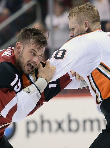 Apr 7, 2018; Glendale, AZ, USA; Arizona Coyotes center Brad Richardson (15) fights Anaheim Ducks right wing Corey Perry (10) during the second period at Gila River Arena. Mandatory Credit: Joe Camporeale-USA TODAY Sports