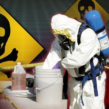A person dressed in a HAZMAT outfit works outside a home.