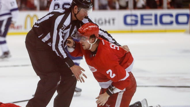 Red Wings defenseman Brendan Smith is helped off the ground after getting into a fight with Tampa Bay at the end of Game 3 Sunday.
