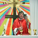 Father Tommy Conway presents the sacrament during a Palm Sunday Mass at St. Fabian's temporary location in Benedict Day School.