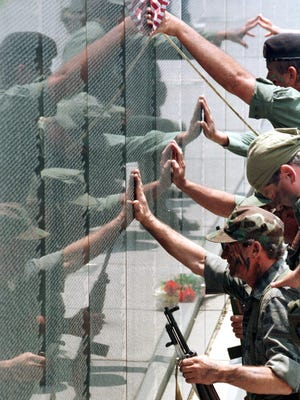 In 1998, members of The Last Patrol are reflected in the stone panels of The Wall South as they pay tribute to their fallen comrades from the war in Vietnam during Memorial Day observances organized by The Vietnam Veterans Motorcycle Club of America.
