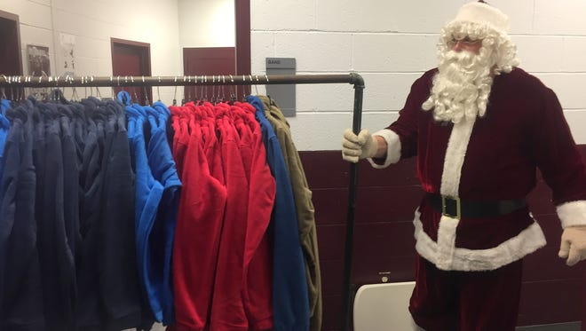 Santa, known to some by his nickname Jack Hancock, helps move a bunch of brand new Columbia jackets waiting to be given to kids at last year's Goodfellows Christmas party in 2017..