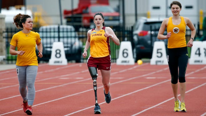 Sammie Gehl runs the 200m dash with a prosthetic leg in the company of associate head coaches Kristine Wolcott on the left and Angela Ryck at St. John Fisher College. She graduated from Horseheads High School in 2016, where she competed in cross country and track until discovering she had bone cancer. After losing one of her legs and learning to walk on a prosthetic, she wanted to return to running and was welcomed by the program at Fisher.