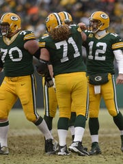 Green Bay Packers quarterback Aaron Rodgers celebrates with his offensive line after the Packers scored a touchdown against the Dallas Cowboys in the third quarter during Sunday's NFC divisional playoff game at Lambeau Field.  Evan Siegle/Press-Gazette Media