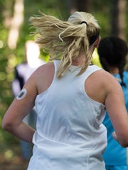 A continuous glucose monitor attached to the back of Emily Cook's left arm helps the Dover High cross-country runner track her blood sugar levels during a race or workout.