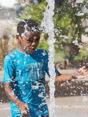 Taye Adams, 8, plays in the fountain after the ribbon cutting and placard dedication for Henery and Caroline Kiser Gustafson and Cynthia Ott-Askew, Friday August 24, 2018.