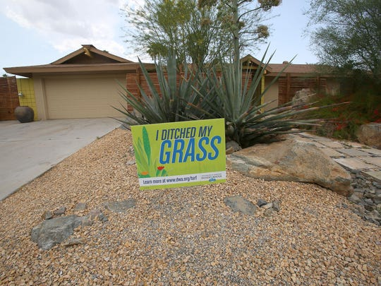 A sign at a home on Sonora Drive in Palm Springs shows where a lawn has been replaced with desert landscaping.