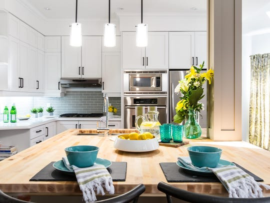 New paint, light colored custom cabinetry, a fireplace, stainless steel appliances, and a contemporary layout with large center island and breakfast nook make this new kitchen the central hub of the home, as seen on HGTV's Buying and Selling. (After #16)