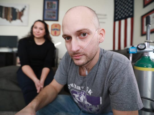 Heath Robinson, of Pickerington, suffered from exposure to toxic smoke from trash-burning pits while serving in the Middle East. He suffered from a rare cancer and died on May 6. His wife, Danielle, is pictured behind him.