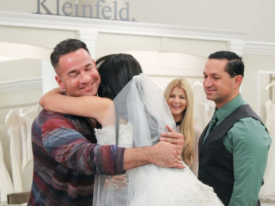 Mike Sorrentino hugs Melissa Sorrentino while brother Marc looks on.