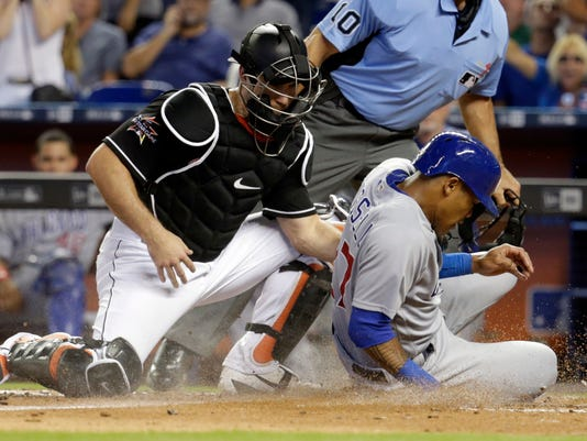 Chicago Cubs' Addison Russell, right, scores past Miami Marlins catcher J.T. Realmuto on a single by Javier Baez during the fourth inning of a baseball game, Saturday, June 24, 2017, in Miami. (AP Photo/Lynne Sladky)