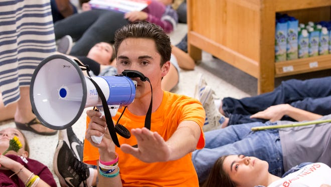 """Marjorie Stoneman Douglas High School student David Hogg speaks as demonstrators lie on the floor at a Publix Supermarket in Coral Springs, Fla., Friday, May 25, 2018. Students from the Florida high school where 17 people were shot and killed earlier this year did a """"die in"""" protest at a supermarket chain that backs a gubernatorial candidate allied with the National Rifle Association. Shortly before the the """"die-in"""" Publix announced that it will suspend political donations. (AP Photo/Wilfredo Lee)"""