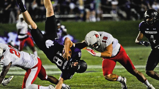 Northwestern quarterback Clayton Thorson is upended by Ball State cornerback Darius Conaway, left, and linebacker Ben Ingle during the first quarter last Saturday in Evanston, Ill.,