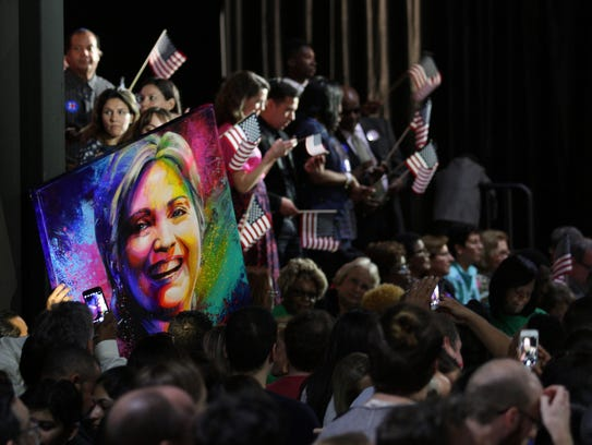 Supporters of Hillary Clinton hold up a large poster