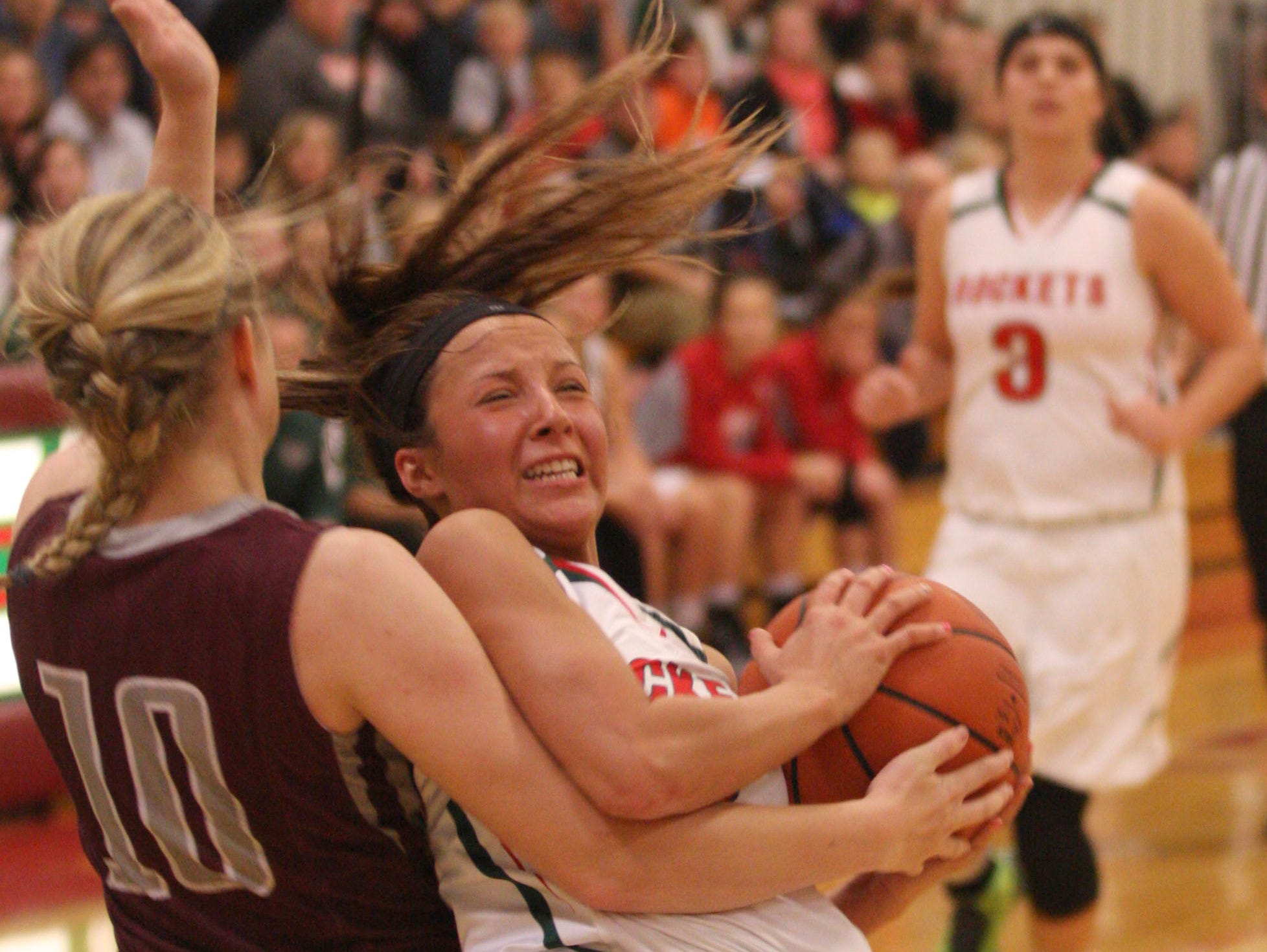 Oak Harbor's Athena Eli tries to maintain her footing and grip on the ball Tuesday against Genoa's Haley Gerke.