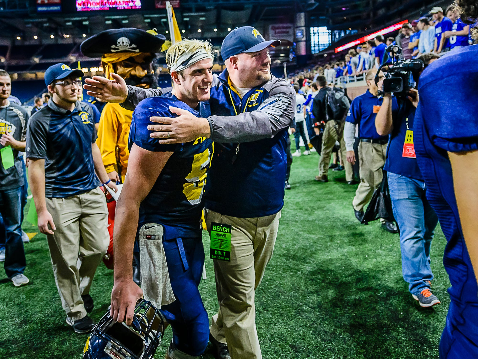Pewamo-Westphalia Head Football Coach Jeremy Miller celebrates with senior lineman Devon Pung as they walk off the field after their Division 7 state final win over Detroit Loyola Saturday November 26, 2016 at Ford Field in Detroit.