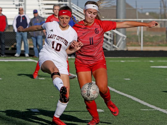 Wichita Falls High School's Alyssa Salinas (10) passes next to Grapevine's Taylor Dellosso (11) Tuesday, April 3, 2018, in the Region I-5A area round at Bull Memorial Stadium in Bridgeport.