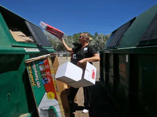 Jennifer Malone recycles cardboard boxes on Monday at Waste Management's Recycling Center in Farmington. The Farmington City Council on Tuesday will vote on whether to allow public comment on a proposal to slightly increase residents' trash rates.