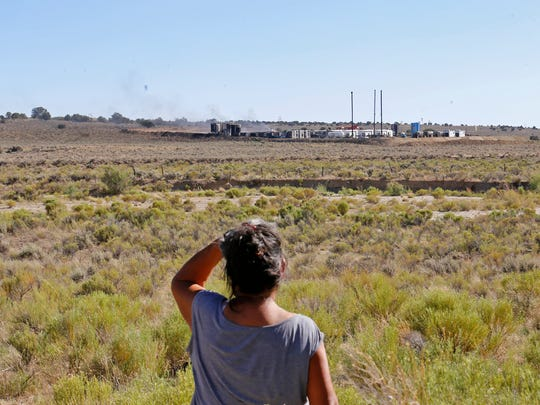 While standing outside her home in Nageezi on Wednesday, Marie Chavez-Herbert watches smoke rise in the distance from a fire at a WPX Energy oil production site that has been burning since Monday night.