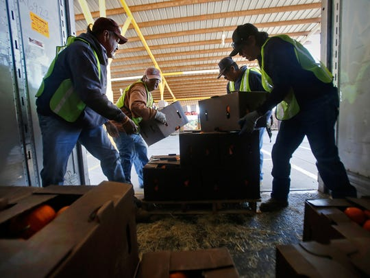 Pumpkin Patch Fundraisers workers pack a truck with products Wednesday at their facility south of Farmington on Wednesday.