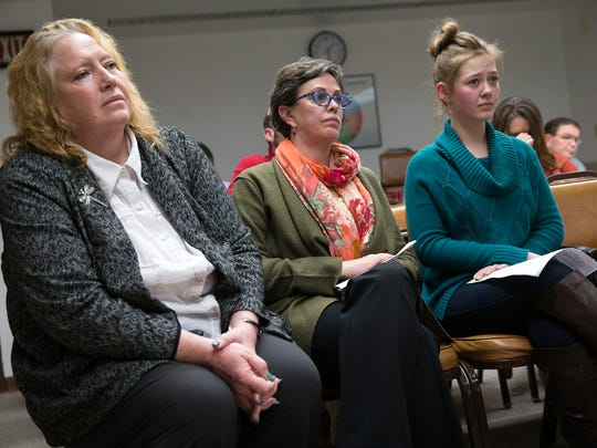 New Mexico Virtual Academy Director Carla Morález, left, academy staff member Rebecca Heilman and student Jordan Patterson listen on Friday as Farmington Municipal School District Superintendent Gene Schmidt announces his recommendations for the academy at a special board meeting at the district's central office.