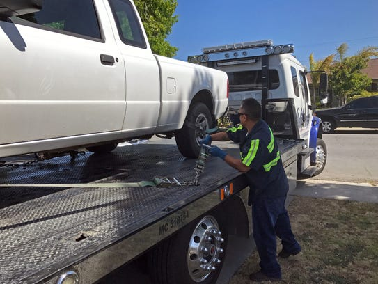 Miguel Gonzalez of California Towing securing a truck