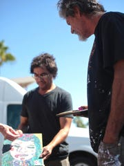Fellow artist, Andrew Esquivel Toscano, admires Staich's oil pastel piece in Palm Springs on June 1. Local artists, Toscano and Donald McPherson, provide 'Scratch' with the use of their personal art studio in Palm Springs.