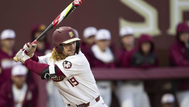 Florida State NCAA college baseball outfielder Elijah Cabell (19) bats against the Univ. of Cincinnati, Friday, Feb. 21, 2020, in Tallahassee, Fla. If all had gone as he hoped, Cabell and his Florida State teammates would be playing for the College World Series championship this week. Instead, Cabell treks to a ball field in his neighborhood in Winter Park, Florida, most days to work on his game in solitude.