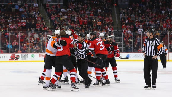 The Philadelphia Flyers and the New Jersey Devils fight