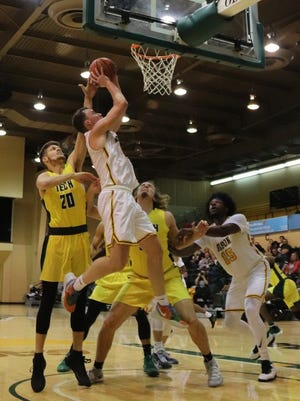 Oklahoma Baptist University's Brantley Thompson (10) goes in for a contested shot while teammate Dishon Lowery (15) goes in for a possible rebound against Arkansas Tech on Saturday.     PHOTO BY BRIAN JOHNSON
