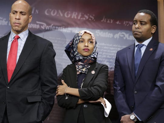 "From left, Sen. Cory Booker, D-N.J., Rep. Ilhan Omar, D-Minn., and Rep. Joe Neguse, D-Colo., listen to remarks by Sen. Bernie Sanders, I-Vt., and other Democrats as they prepare to introduce new legislation to reduce what Americans pay for prescription drugs, especially brand-name drugs deemed ""excessively priced,"" during a news conference on Capitol Hill in Washington, Thursday, Jan. 10, 2019. (AP Photo/J. Scott Applewhite)"