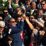 """Ahmed Zayat, owner of American Pharoah, holds up the Kentucky Derby trophy. """"This is one special horse. I was very reluctant to hype him, but the horse does the talking,"""" he said. """"We are very privileged to have an unbelievable trainer (Bob Baffert). This is a dream come true."""""""