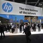 Angel Navarette, Bloomberg News Attendees pass the Hewlett-Packard Co. (HP) pavilion on day two of the Mobile World Congress in Barcelona, Spain, on Tuesday, Feb. 25, 2014. The company announced Wednesday that it will be splitting into two companies.