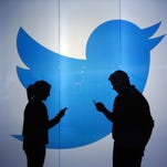 People are seen as silhouettes as they check mobile devices while standing against an illuminated wall bearing Twitter Inc.'s logo in this arranged photograph in London, U.K., on Jan. 5.