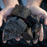 """Locust Grove Inc. mine contractor Jabo Clemons, a descendant of a long line of coal miners in Perry County, scooped coal into his hands on a TECO Coal mine site in Hazard, Ky, in 2012. """"There's nothing to replace coal,"""" Clemons said. Oct. 25, 2012"""