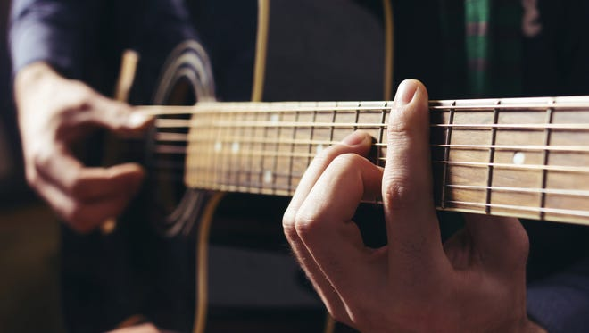 Man playing music at black wooden acoustic guitar.