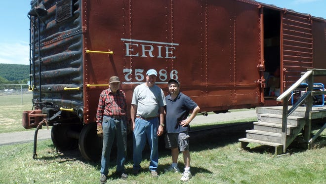 Members of the Chemung Valley Railway Historical Society show off a restored 1928 Erie Railroad boxcar at Elmira's Eldridge Park.