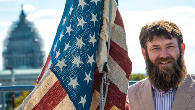 Mike Lewis holds a flag made from hemp in DC on Veterans Day.