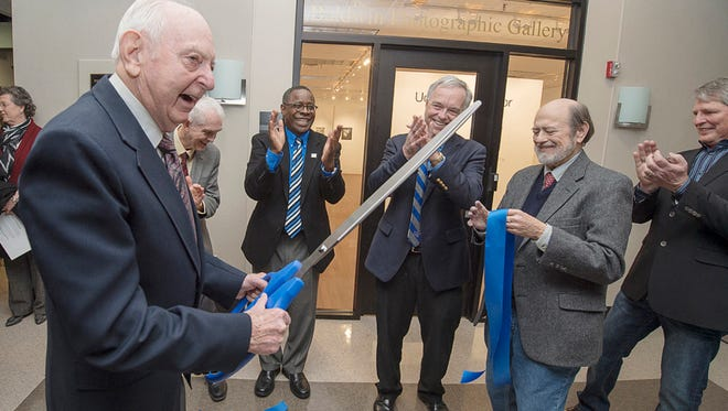 MTSU Professor Emeritus Harold Baldwin jokes with the audience after cutting the ribbon on the new site of the photo gallery that bears his name Monday night in the Bragg Mass Communication Building. Baldwin Photographic Gallery curator Tom Jimison is at center right holding the ribbon. Also celebrating are from left, behind Baldwin, Roy Moore, former dean of the College of Mass Communication; MTSU President Sidney A. McPhee; current mass comm dean Ken Paulson; and Billy Pittard, chair of the Department of Electronic Media Communication. (MTSU photo by Andy Heidt)