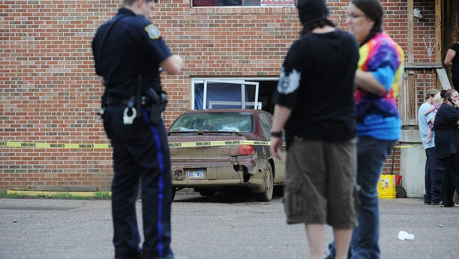 Sioux Falls Police officers on scene after a hit-and-run accident on the 600 block of South Dakota Avenue that damaged a parked vehicle and an apartment building on Monday, May 25, 2015, in Sioux Falls. One person sustained minor injuries in the accident, and police are looking for a white suspect vehicle.