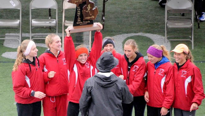 Members of St. Johns girls track and field team celebrate their Division 2 state title Saturday.