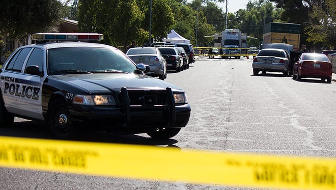 Mesa police line the 1000 block of West Drummer Avenue, in Mesa, Sunday morning after a woman was found dead along the sidewalk.