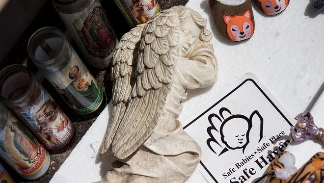 A sticker from Safe Haven, candles, toys and an angel statue line the bottom of a makeshift memorial made by mourners of a dead newborn infant found inside a Glendale dumpster on Aug. 15, 2015.